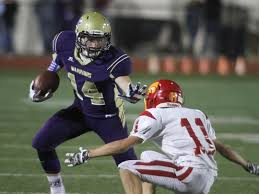 Tyler Schamel #14 of Norwalk HS applying a stiff arm to a defender